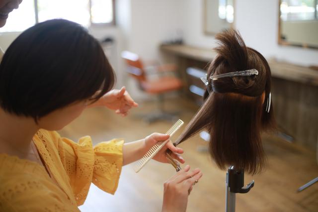 カットの練習をする美容師